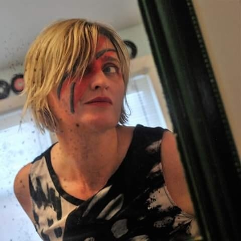 Image of a woman looking in the mirror with a lightning bolt painted across her face