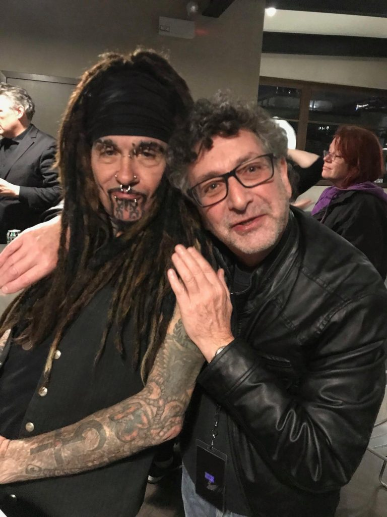 A man in eyeglasses hugs a man with dreadlocks and facial piercings in a candid photograph