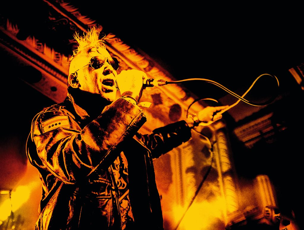 Yellow and black image of a man with a mohawk on stage with a microphone